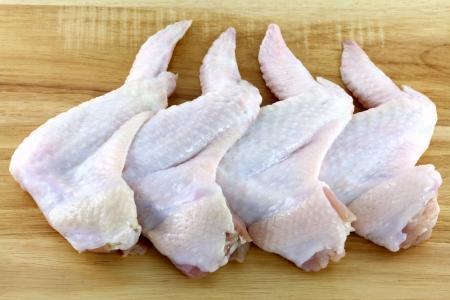 alitas de pollo: Alas enteras crudas y frescas de pollo en una tabla para cortar madera