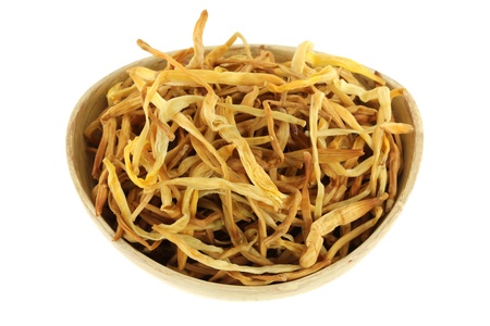 lily buds: Closeup photography of Chinese medical herb   A bowl of Dried Lily Buds  Lily flower isolated on white