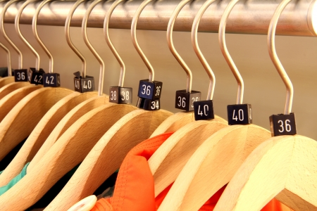 Close up of a clothing rack with wooden hangers showing different clothing size tags