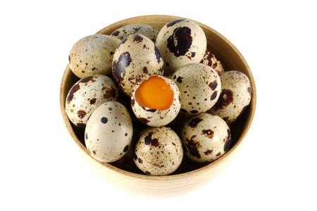 huevos de codorniz: Un tazón de fuente de madera por completo de huevos de codorniz frescos, uno se abre para mostrar la yema