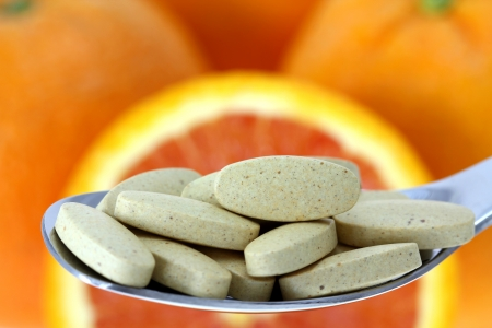 Film Coated Tablets of Vitamin C on the Orange background