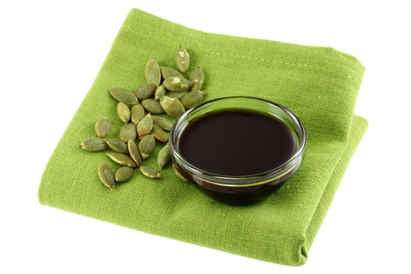 A Glass bowl of Pumpkin Seed Oil and some Roasted Pumpkin Seeds