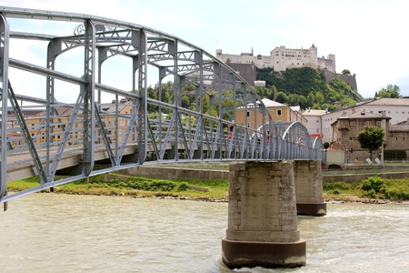 The Mozartsteg, an art nouveau bridge over Salzach river in Salzburg with the background of fortress Hohensalzburg photo
