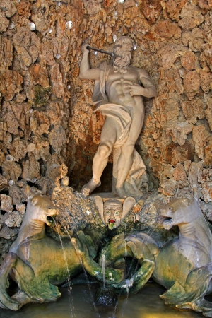 automat: Salzburg, Austria - August 14, 2012   Neptune�s Fountain with a water automat face beneath the statue inside the Neptune grotto at Schloss Hellbrunn, a Waterpark at the Summer Palace in Salzburg, Austria