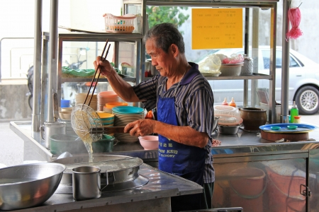 Penang, Malaysia - April 18, 2012   A man making noodles at Mee noodle stall on Lorong Kampung Malabar street in Penang, Malaysia