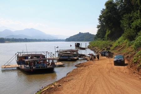 Luang Prabang, Laos - 29 December 2012   People using local ferry to transport vehicles cross the Mekong River in Luang Prabang, Laos