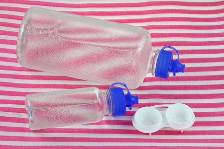 disinfecting: Bottles of Multi-Purpose Contact Lens Solution and a lens case