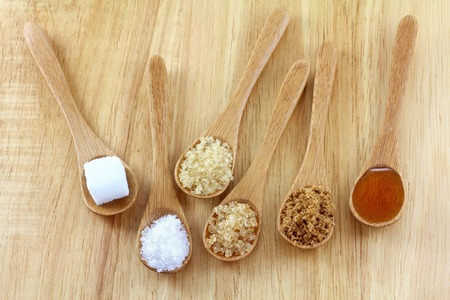 fine cane: Spoons of different type of sugar on the wooden background