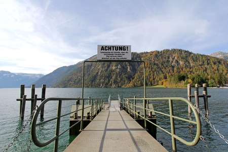 metres: TYROL, AUSTRIA - OCTOBER 2013    A pier for boat trips on Achensee Lake during Autumn on October 20, 2013 in Tirol, Austria  The Achensee is the largest lake within the federal state, and has a maximal depth of 133 metres