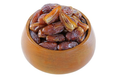 deglet: A wooden bowl full of natural dried Deglet Nour dates from Israel Stock Photo