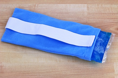 relieve: A blue reusable soft gel-filled cold and hot pack to relieve pain inside a fabric pouch  Stock Photo