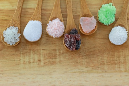 himalayan salt: Spoons of commercial salt and natural rock salt on a wooden background Stock Photo