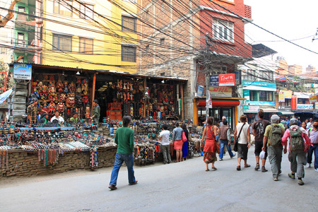 singing bowls: Tourists walking along souvenir shops in in Kathmandu, Nepal. Many of souvenir shops sell masks, knives, singing bowls, prayer wheels, bead necklaces.