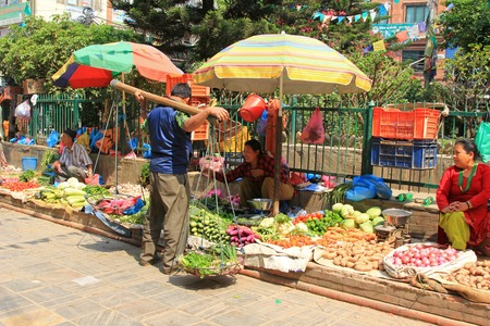 street life: A vegetable hawker with his Kharpan chitchatting with Nepalese street venders in Kathmandu, Nepal. Most of the products are fresh vegetable.