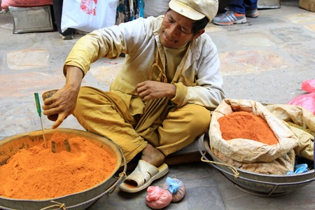 almost all: A street vendor selling ground turmeric, cumin, red pepper in a metal Kharpan in Kathmandu, Nepal. His clothes are stained with turmeric powder, one of the main herbs that is used in almost all Nepali dishes.