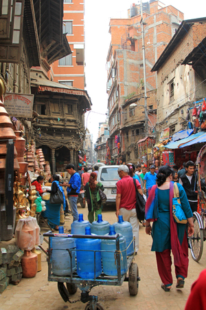 occupying: Vehicles and people occupying a busy shopping street named Ason Tole in Kathmandu, Nepal