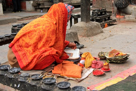 reciting: PATAN, NEPAL - APRIL 2014 : A prayer reciting a holy book at Kumbeshwar Temple on 13 April 2014 in Patan, Nepal. Kumbeshwar Temple is the oldest temple in Patan which was built in 1392.