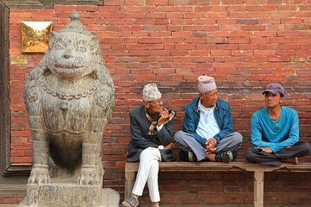 darbar: Patan, Nepal - aprile 2014: gli uomini nepalesi seduta accanto a un leone di pietra, a guardia del Sun Dhoka (Golden Gate), l'ingresso al Museo Patan Patan, Nepal il 13 aprile 2014. Patan Museum � un'antica corte residenziale di Patan Darbar , uno dei pala reale