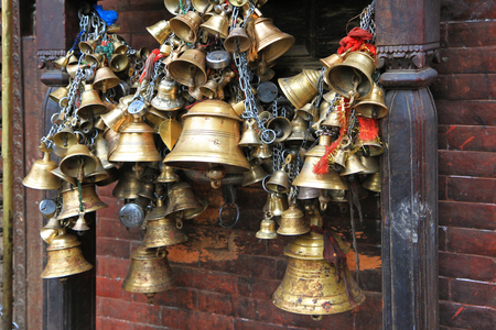 hindu goddess: PATAN, NEPAL - APRIL 2014 : Metal sacrificial bells hanging on chain at Kumbeshwar Temple on 13 April 2014 in Patan, Nepal. Bell is one of the worship materials to Hindu Goddess. Editorial