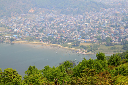 tal: View of Pokhara city at foot of Annapurna range along the Phewa Lake in Pokhara city, Nepal. Photo taken from Ananda Hill, World Peace Pagoda