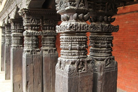 PATAN, NEPAL - APRIL 2014 : Beautifully carved wooden pillars at Patan Museum in Patan, Nepal on 13 April 2014. Patan Museum is an old residential court of Patan Darbar, one of the royal palaces of the former Malla kings of the Kathmandu Valley.