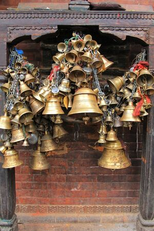 hindu goddess: Metal sacrificial bells hanging on chain at Kumbeshwar Temple in Patan, Nepal. Bell is one of the worship materials to Hindu Goddess. Editorial