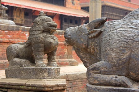 PATAN, NEPAL - APRIL 2014 : A statue of cow and snow lion at Patan Darbar Square on 13 April 2014 in Patan, Nepal Editorial