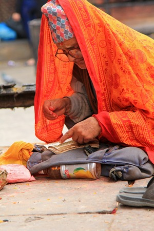 reciting: A prayer reciting a holy book at Kumbeshwar Temple in Patan, Nepal. Kumbeshwar Temple is the oldest temple in Patan which was built in 1392. Editorial