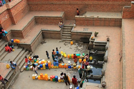 waterspout: People gathering at Sunken Manga Hiti - Water Conduit with carved stone Makara (mythical crocodile-elephants) waterspouts in Patan, Nepal. People gather daily with water containers for household use.