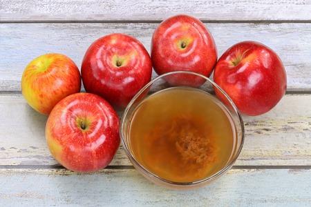 manzana: Manzanas frescas y una taza de vinagre de sidra de manzana org�nica cruda y sin filtrar con enzimas madre Foto de archivo