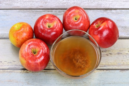 Fresh apples and a bowl of raw and unfiltered organic apple cider vinegar with mother enzymes Archivio Fotografico