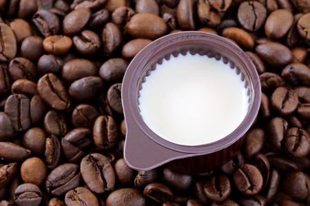 creamer: A small cup of Coffee Creamer on coffee beans