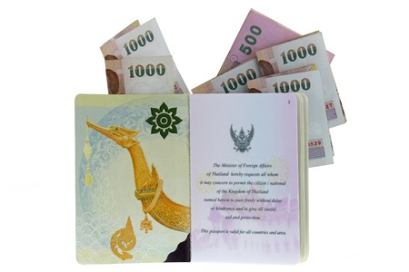 issued: Thai electronic passport (issued by a government in Thailand), with folded 500 and 1000 Baht Banknotes, isolated on white background Stock Photo