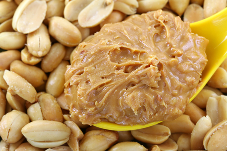 sandwich spread: A spoon of creamy crunchy peanut butter on roasted nuts