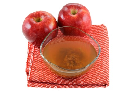 enzymes: Fresh apples and a bowl of raw and unfiltered organic apple cider vinegar with mother enzymes isolated on white