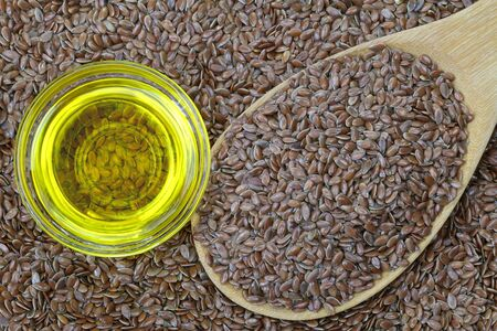 flaxseed: A bowl of cold pressed Linseed yellow oil on flaxseed background. flaxseed are seeds from flax plant.