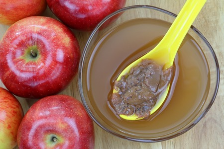 enzymes: Fresh apples and a bowl of raw and unfiltered organic apple cider vinegar with mother enzymes on a wooden background