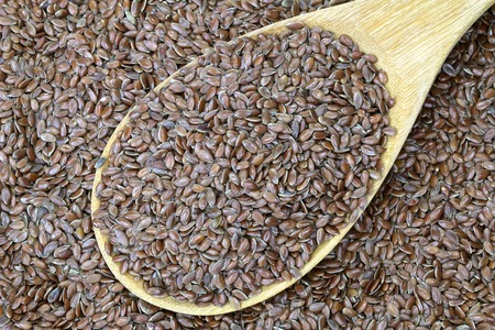 unsaturated: A wooden spoon full of Linseed (Flaxseed). Flaxseed are seeds from flax plant. Stock Photo
