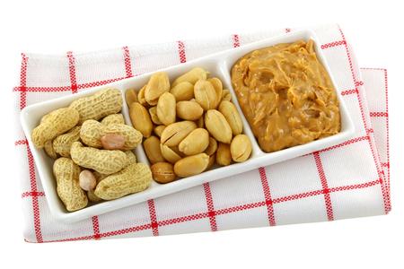 grasas saturadas: Un plato de man� tostado, man� salado y mantequilla de man�, aislado en blanco