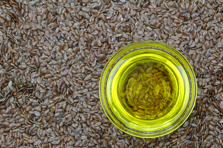 A bowl of cold pressed Linseed yellow oil on flaxseed background. flaxseed are seeds from flax plant photo