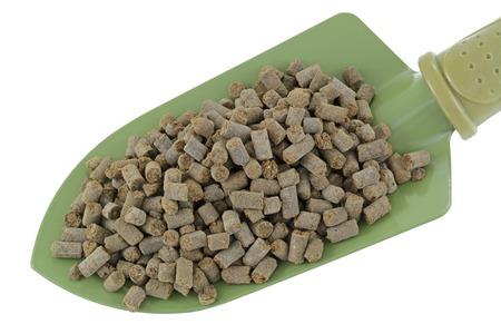manure: A shovel full of compressed Organic Animal-based Fertilizer Pellets isolated on white
