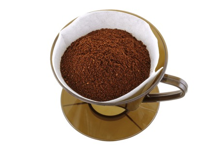 papel filtro: Un cono de caf� marr�n con papel de filtro lleno de caf� molido fresco