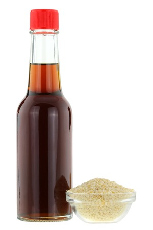 white sesame seeds: A bottle of cold pressed Sesame oil next to a bowl of white Sesame seeds, isolated on white background