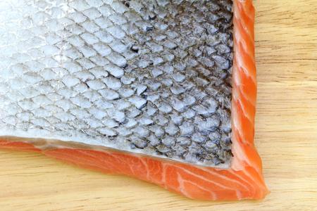 flesh eating animal: Closeup photo of Raw salmon with skin on wooden cutting board Stock Photo