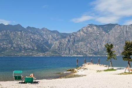 sanremo: People enjoy sunbathing in the summer near the Albergo Sanremo pier at the Garda Lake  Lago di Garda in Italy