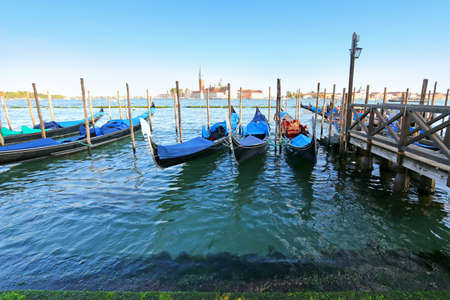 moorings: Gondolas at their moorings in the evening in Canale di San Marco, Venice, Italy. San Giorgio Maggiore can be seen on the background.