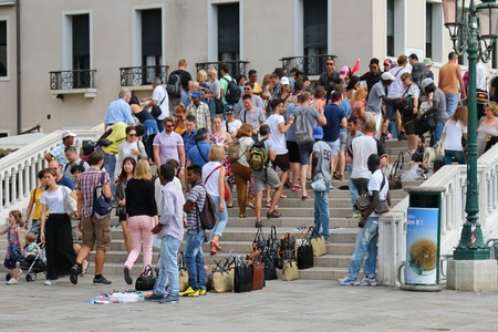 designer bag: Tourists walking pass vendors that sell fake hi-end fashion brand name bags and purses in Venice, Italy on September 15, 2014. Editorial