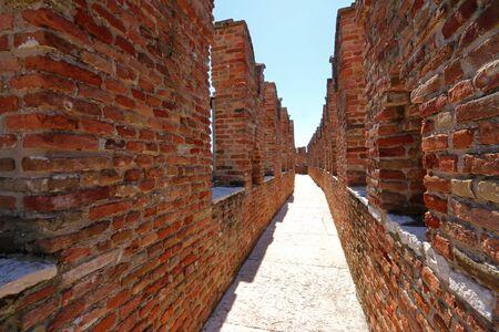 edad media: Un pequeño camino entre las paredes de la famosa y antigua de ladrillo Castillo Fortaleza de Castelvecchio en Verona, norte de Italia el 14 de septiembre de 2014. Castelvecchio fue construido en 1354 por el Scaliger Cangrande II durante la Edad Media. Editorial