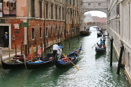 means of transportation: Gondoliers with their rowing oar carrying tourists on Venetian canals in Venice, Italy on September 15, 2014. Gondola boats is still the main means of transportation in Venice. Editorial