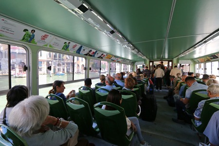 waterbus: Passengers sitting inside public water taxi or water bus Vaporetto in Venice, Italy on September 15, 2014. Different colors of line indicates different routes. There are Blue, Red, Green, and this one, Orange line Editorial